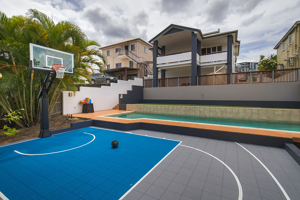 Blue and grey backyard basketball court with pool and high set house
