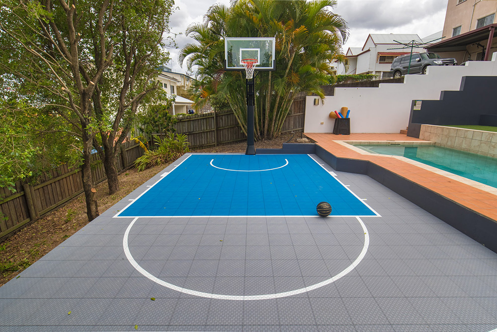 Blue and grey backyard basketball court next to a swimming pool