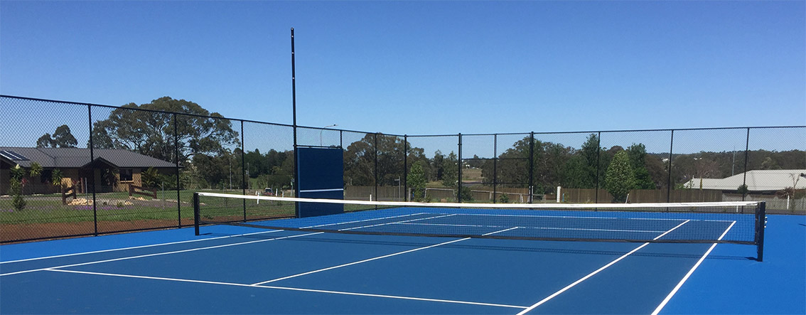 Blue tennis court with chainlink fencing on sunny day