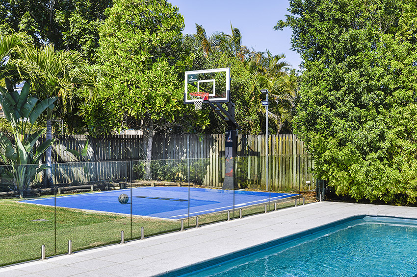 Blue basketball court and basketball post in Aussie backyard with swimming pool