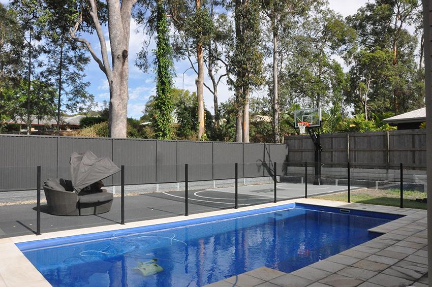 Grey backyard basketball court next to a swimming pool