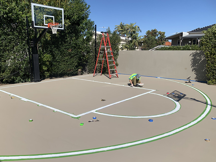 Man line-marking a brown basketball court on a sunny day
