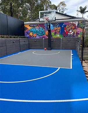 blue and grey backyard court with basketball backboard and graffiti wall