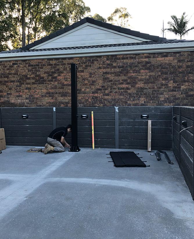 man installing a basketball onto a concrete slab