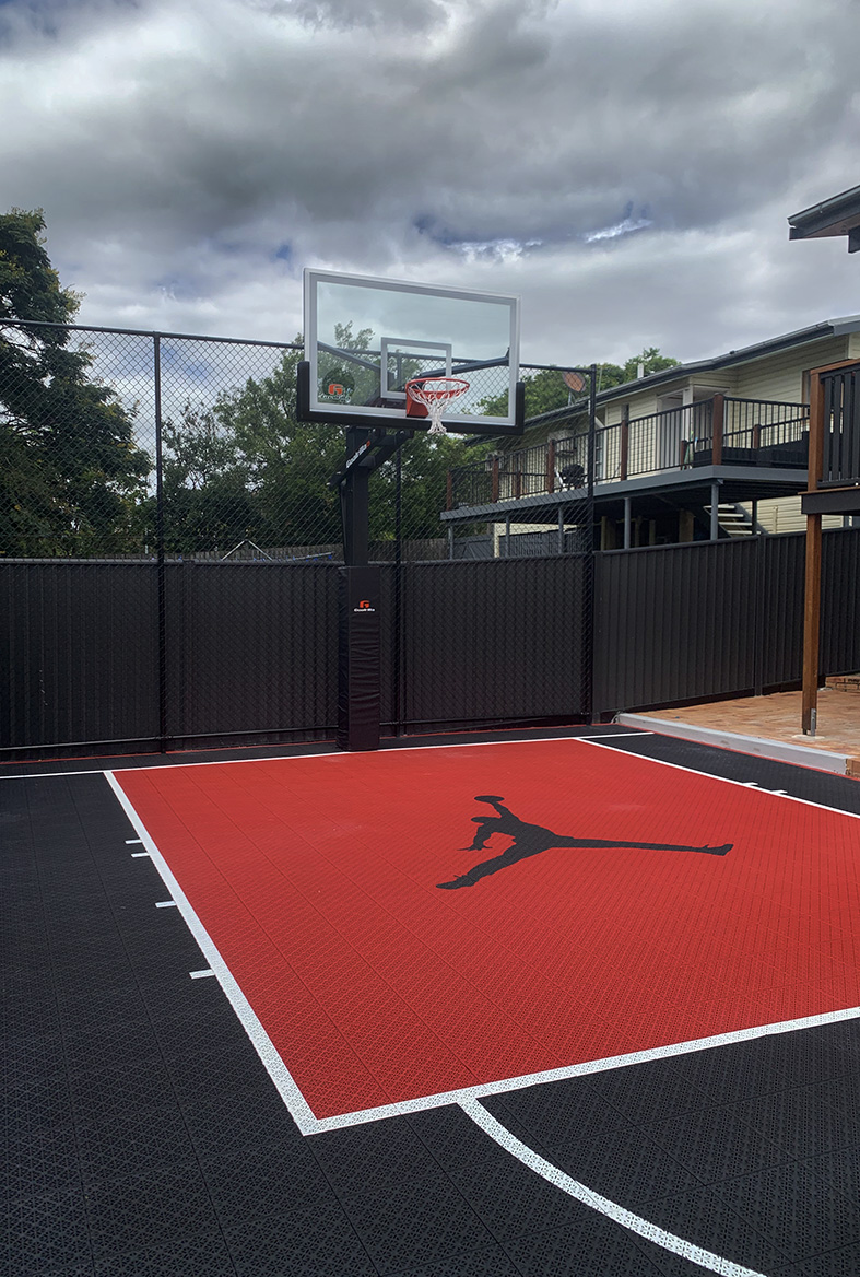 red and black basketball court in backyard