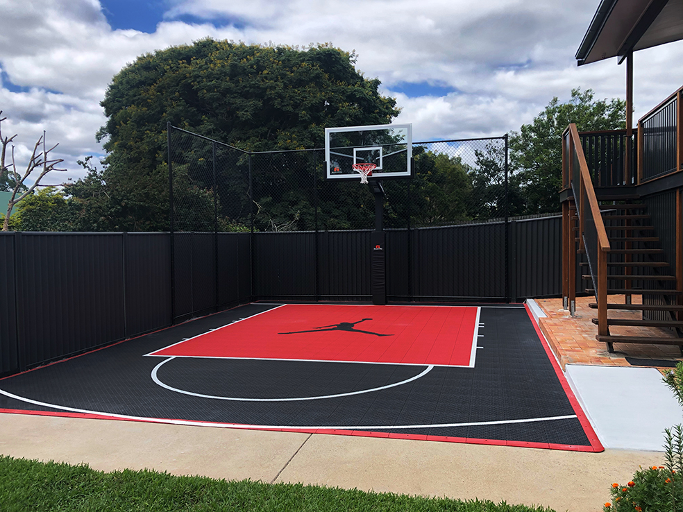 red and black basketball court in suburban backyard