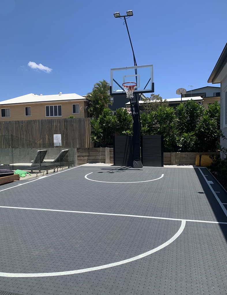 grey basketball court with basketball post and light above it