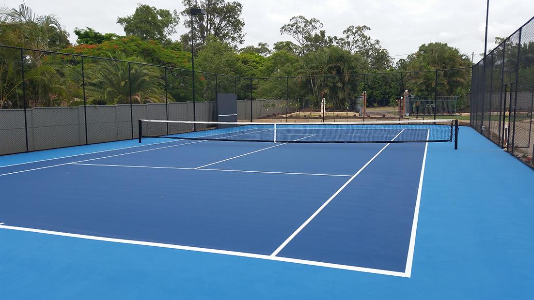 blue tennis court with gardens