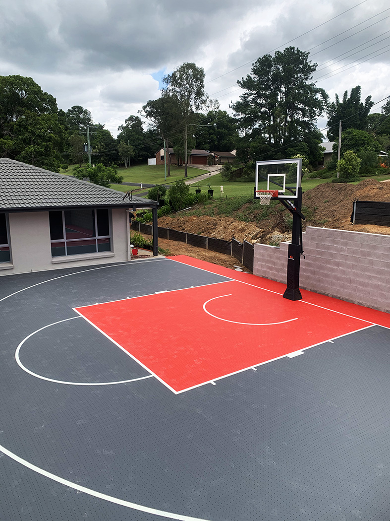 red and grey basketball court in Brisbane backyard in front of a modern house