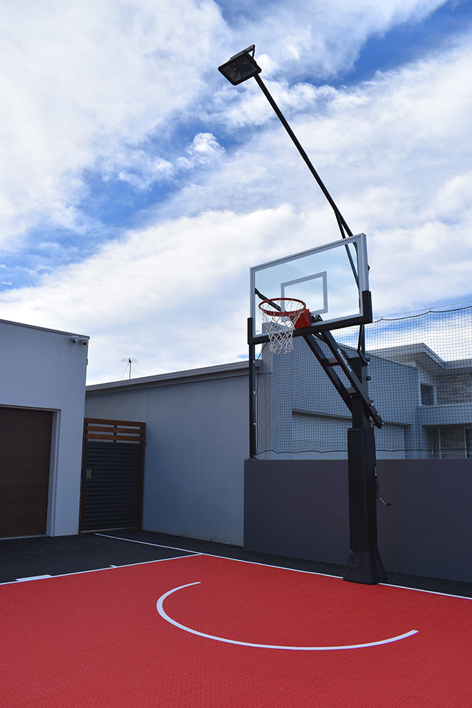 black and red basketball court with basketball post with light